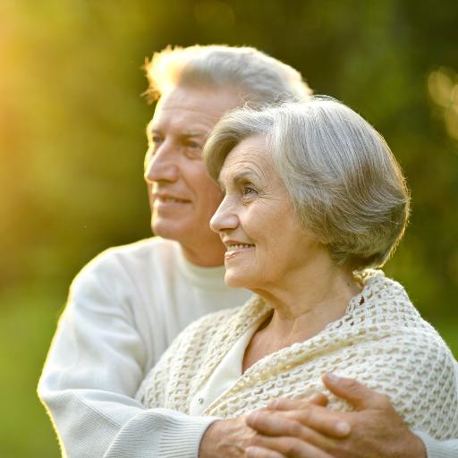 Ein älteres Paar schaut zufrieden in die Natur.