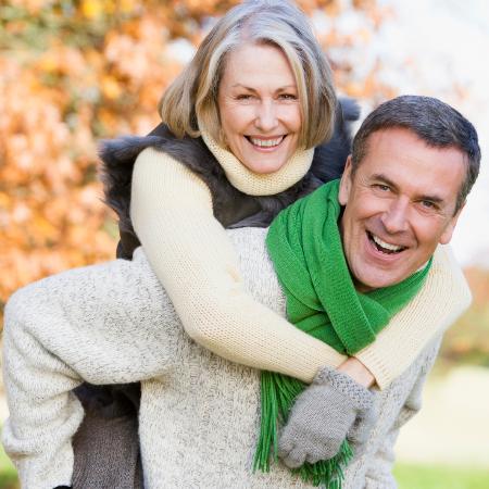 Ein älteres Ehepaar: Der Mann trägt die Frau auf dem Rücken, beide strahlen in die Kamera.