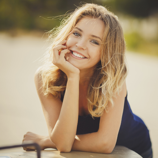 Eine junge Frau lacht in die Kamera.