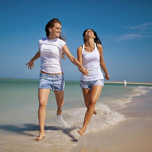 Zwei Freundinnen rennen am Meer entlang und lachen.