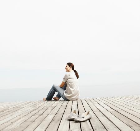 Frau sitzt auf einem Steg, schaut in die vernebelte Natur.